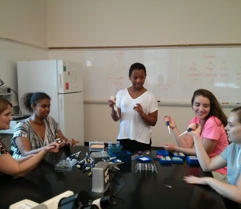 A professor, three students, and an Undergraduate Teaching Assistant practice using pipettes.