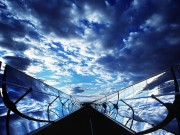 A New Mexico sky is reflected in the curved mirrors of a parabolic trough, used to focus energy on a long glass tube, Sandia National Laboratories. US Department of Energy, US government work.