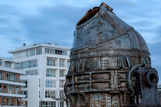 """The area of former steel factory """"Phoenix Ost"""" was turned into an artificial lake surrounded by office and apartment buildings. A former converter (a device to make steel from iron), shown in the picture in front of the new buildings, was placed on the lake shore as a monument."""