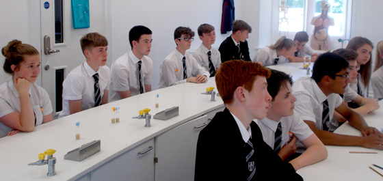 Photo of school students with vials of Drosophila