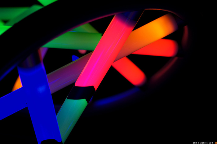 Closeup photo of DNA structure model with base pairs represented by glowing neon bars.