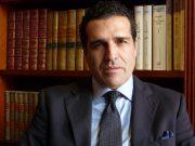 Gonzalo Castro de la Mata medium shot, behind desk and in front of a bookshelf
