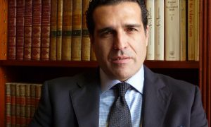 Gonzalo Castro de la Mata medium shot, behind desk and in front of a bookshelf