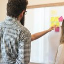 A man and a woman stand in front of a large whiteboard with sticky notes on it. Someone is explaining or teaching something on the board to the two people.