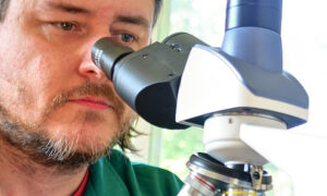 Stephen Klusza with a microscope